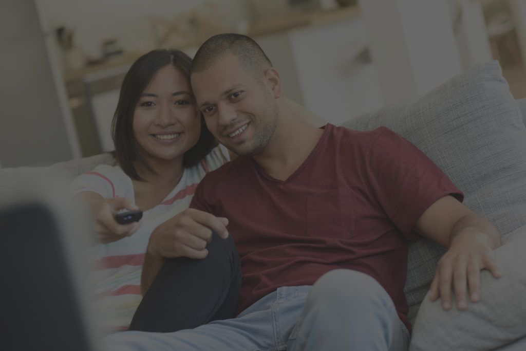 Couple at home in sofa watching movie on tv